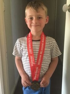 Jades son Isaac wearing her medal from her marathon last year